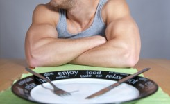 13275526 - muscular man sitting at the table with empty plate